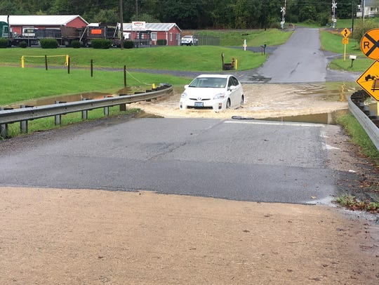 A car drives through the high water on Jericho Road