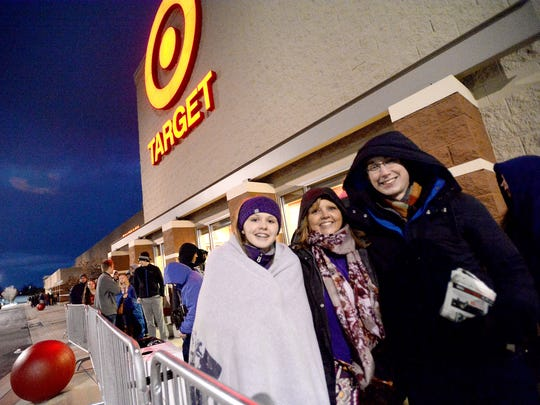 Melanie Hartless of Verona stands between daughter Amanda Humphreys, 14, and son Tyler Humphreys. They brave the cold as they stand in the line shoppers waiting for Target's 6:00 p.m. opening on Thanksgiving night for Black Friday savings in Waynesboro on Thursday, Nov. 27, 2014.
