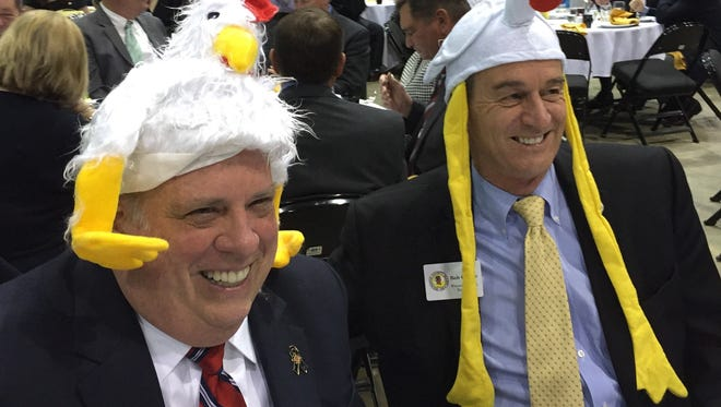 This April 20, 2016 photo shows Maryland Gov. Larry Hogan and Wicomico County Executive Bob Culver trying on goofy chicken hats at the annual Delmarva Poultry Industry, Inc. annual banquet in Salisbury. Hogan, without the hat, brought greetings to the more than 700 guests.