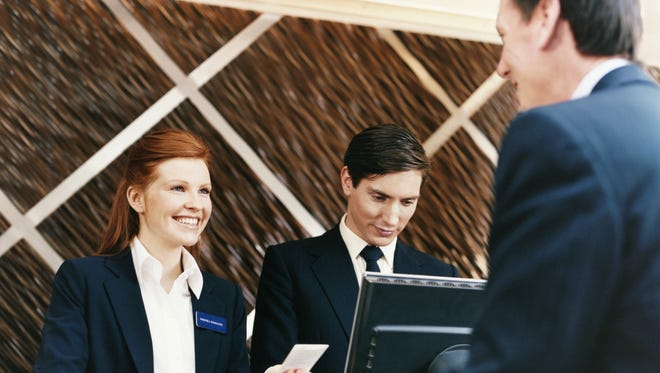 Female Hotel Receptionist Welcomes a Businessman as he Checks Into the Hotel