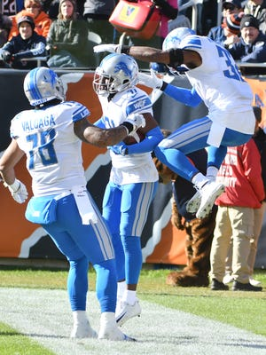 Lions' Jeremiah Valoaga, D.J. Hayden and Tavon Wilson celebrate Hayden's fumble recovery and run into the end zone for a touchdown in the second quarter.
