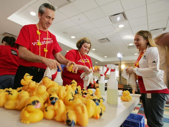 Volunteers help scrub 5,000 rubber ducks May 4 at the