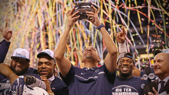 Penn State Nittany Lions head coach James Franklin, surrounded by the Nittany Lions, holds up the Stagg championship trophy after winning the Big Ten championship against the Wisconsin Badgers, at Lucas Oil Stadium, Indianapolis, Saturday, Oct. 3, 2016.
