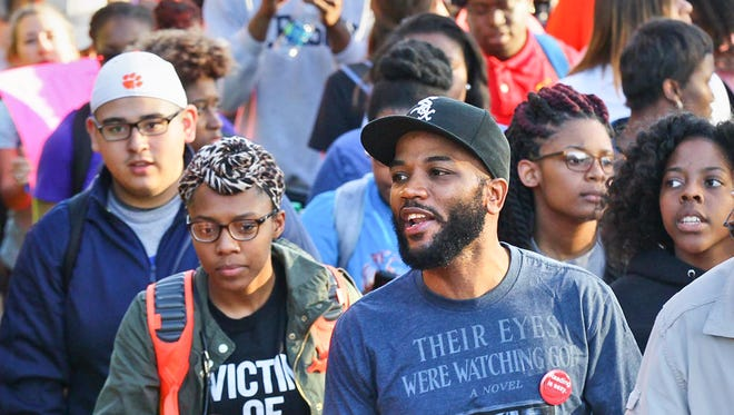 A.D. Carson (middle), one of five Clemson University students released after getting a citation for trespassing in Sikes Hall, leads a march and chant to the front steps of the administration building. Students protested over exclusion, racial insensitivity, and administrative inaction at the university in 2016. Carson earned a doctoral degree in rhetorics, communication and information design in 2017 from Clemson University.