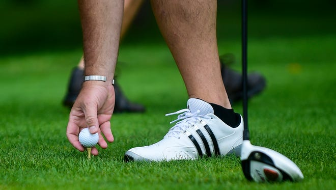 A golfer sets his ball up on a tee. The Marion County Men's Amateur Championship will be held at the Marion Country Club June 23 and 24.