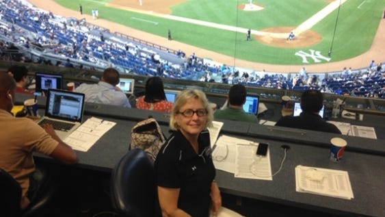 Judy Scarafile enjoys the view from the press box during a 2015 visit to Yankee Stadium. As a college student and scorekeeper for the Cape Cod Baseball League 50 years ago, she was removed from the press box at old Yankee Stadium because no women were allowed.