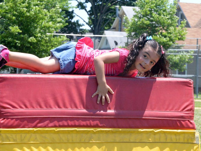 Amariah Morales, 4, of Vineland, rolls over a stack of pads in an obstacle course during a June Jubilee at Sabater School in Vineland on Saturday, June 14, 2014.  Staff photo/Charles J. Olson
