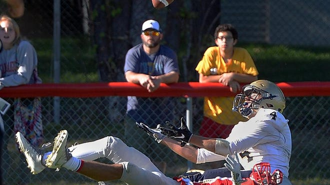Brighton's Owen Davis, top, makes a juggling catch over Canandaigua's Mitchell Pfeiffer for the game-winning overtime touchdown in Canandaigua on Saturday.