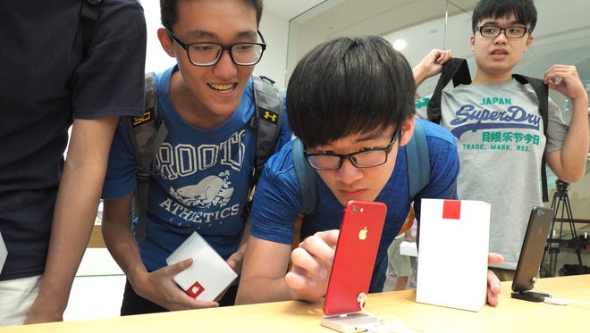 Students look at an iPhone at the Apple Store in the Taipei 101 skyscraper in Taipei, Taiwan.