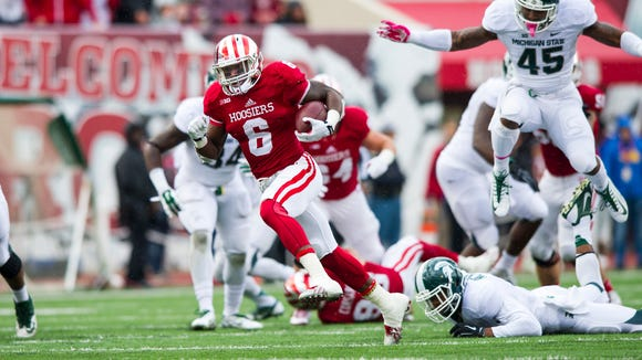 Tevin Coleman (6) rushes the ball into the Michigan State secondary during the first half of action Saturday.