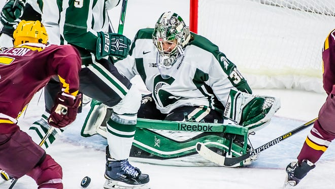 MSU goalie Jake Hildebrand moves to stop a Minnesota shot on goal during their game Friday December 5, 2014 in East Lansing. KEVIN W. FOWLER PHOTO