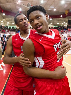 Pike High School senior Jeffery White (34), left, celebrates the victory over Southport with teammate junior Derek Hawthorne (24) after the game. Southport High School hosted two semi-final games of the 2015 Marion County Boys Basketball Tournament, Friday, Jan. 16, 2015. Pike defeated Southport 92-86 in four overtime periods.
