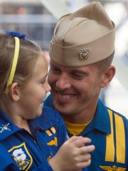 Reagan Davies, left, celebrates the return of her father, Blue Angels pilot, Tyler Davies, right, to Pensacola during a ceremony at the National Naval Aviation Museum Monday afternoon.