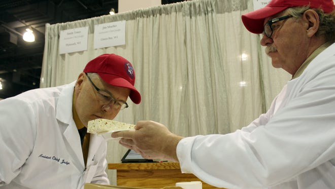 Judge Stan Dietsche, right, lets another judge, Tim Czmowski, smell a flavored feta cheese during the 2015 United States Championship Cheese Contest, Tuesday, March 17, 2015, in Milwaukee. The contest is the biggest ever, with a record 1,885 entries from 28 states.