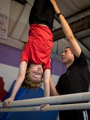 Gymnastics coach Chris Lambert, 18, assists 10-year-old Caden Krauel on the parallel bars at  Cruces Gymnastics Academy.