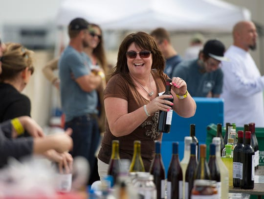 Darlene Perdue of Fort Pierce, cracks open a bottle of wine at the 2015 Groovin' & Tastin' Sunrise City Beer, Wine and Spirits Fest on the top of the parking garage in downtown Fort Pierce. This year's event is 1-5 p.m. Saturday.