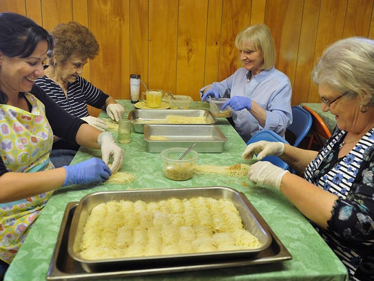 In this file photo, Alexandra Loukou, left, Anthea Atalis, Eleni Moshtaghi and Flora Ataliotism, right, prepare batches of Kataifi at the Holy Cross Greek Orthodox Church. The ladies are preparing for the church's annual Greek Bake Sale Saturday.