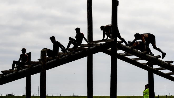 """A group of competitors make their way across """"The Summit"""" Saturday during Garden City Recreation Commission's annual """"The Siege"""", a 5K obstacle course at Garden City High School's JROTC challenge course. Approximately 120 area residents participated in the event."""