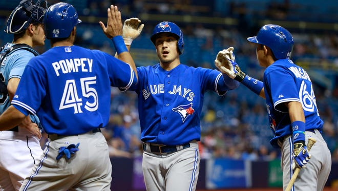 Toronto Blue Jays shortstop Darwin Barney (18) is congratulated by center fielder Dalton Pompey (45) and second baseman Munenori Kawasaki (66) as he hits a 2-run home run during the ninth inning against the Tampa Bay Rays