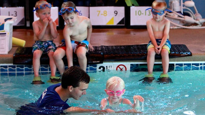 Swimming instructor Jacob Kerr works with Kayleigh Friebe during swimming lessons at DiVentures Scuba & Swim Center.