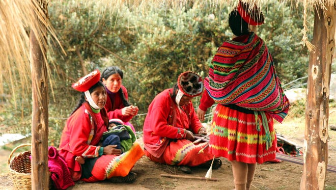 A group of women wear colorful woven clothes in Patacancha, Peru. The village is home to a women's weaving collective that hosts workshops for visitors.
