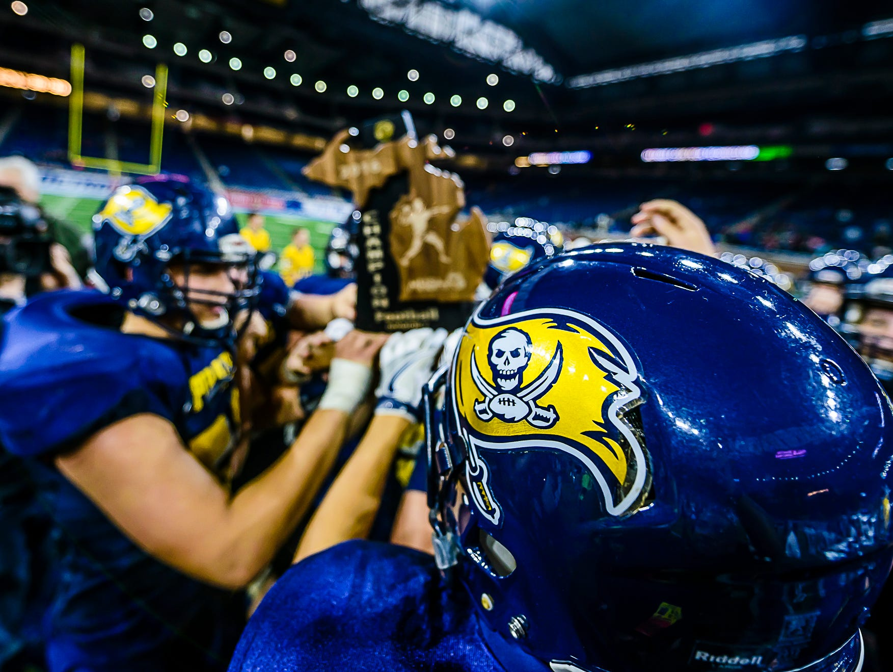 The Pewamo-Westphalia fottball holds the Division 7 state championship trophy after their defeat of Detroit Loyola Saturday November 26, 2016 at Ford Field in Detroit.