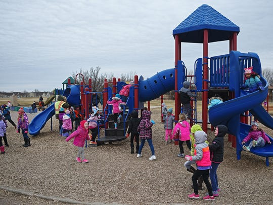 Kindergarteners play on the playground during morning