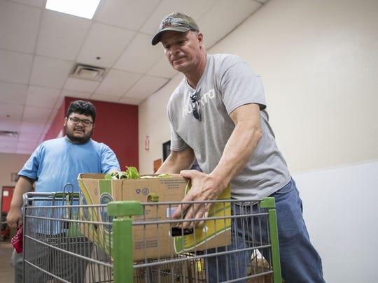 Rob Carson, right, and Alex Suniga volunteer at the