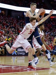 Michigan's Moritz Wagner, top, pulls in an offensive