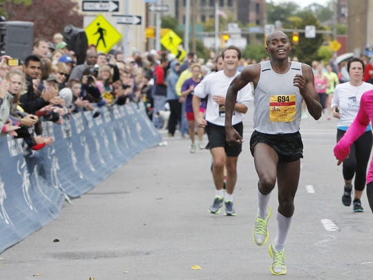 """Kiplangat """"Kip"""" Tisia, of Rochester, center, heads to a top finish with a time of 2:19:59 at the finish line of the 2013 Rochester Marathon."""
