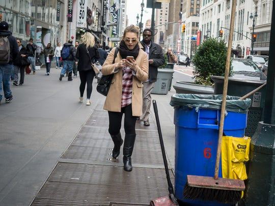 A shopper texts while walking in Midtown Manhattan