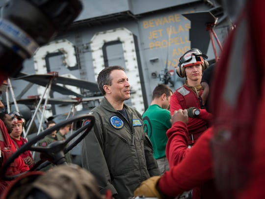 Commanding Officer of the USS Dwight D. Eisenhower, U.S. Navy Capt. Paul C. Spedero, an experienced naval aviator who flew combat missions in support of Operation Iraqi Freedom and Operation Enduring Freedom, on the flight deck talking with red shirted emergency and ordnance crew members.
