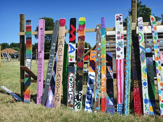 A group of painted fence pickets stand ready to be