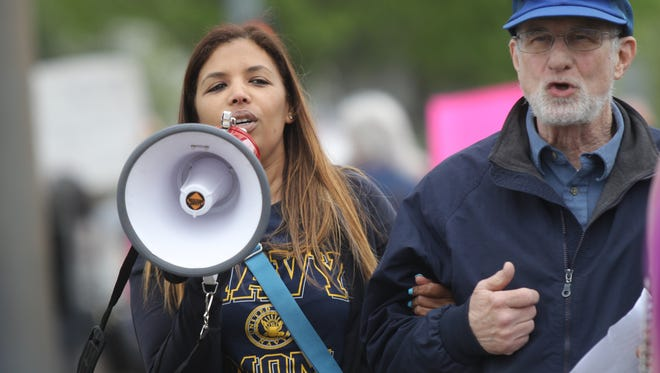 Rosario Urena from Stony Point shouts in a megaphone during a rally for immigrants' rights at the intersection of Route 59 and Middletown Road in Nanuet on Monday, May 1, 2017.