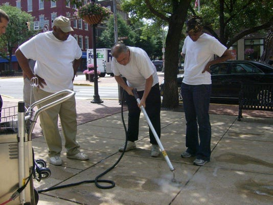 The Downtown Inc cleaning crew is trained on how to use the Dr. Gum machine. From right are Michael Burgesser, Larry Richardson and Teresa Branch.