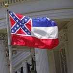 The Confederate flag is unfurled against the front of the Governor's Mansion in Jackson, Miss.