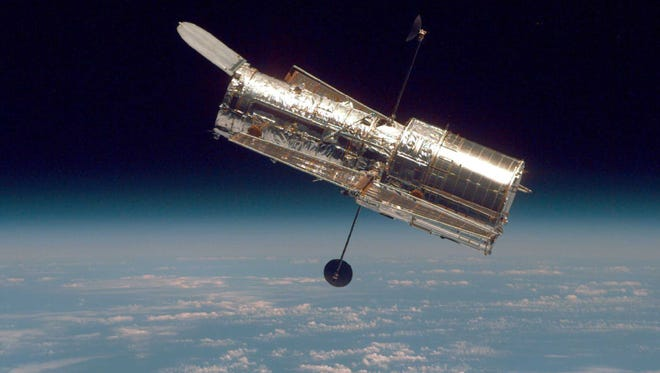 The Hubble Space Telescope drifts through space in a picture taken from the Space Shuttle Discovery during Hubble's second servicing mission in 1997.