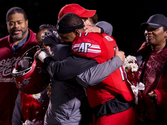 Head Coach Will Healy hugs senior Jeremiah Mitchell,