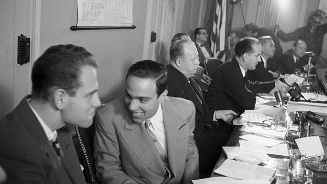 Aides G. David Schine (far right) and Roy Cohn (second from right) horse around as their boss, Senator McCarthy, grills Theodore Kaghan of the US Information Agency in 1953.
