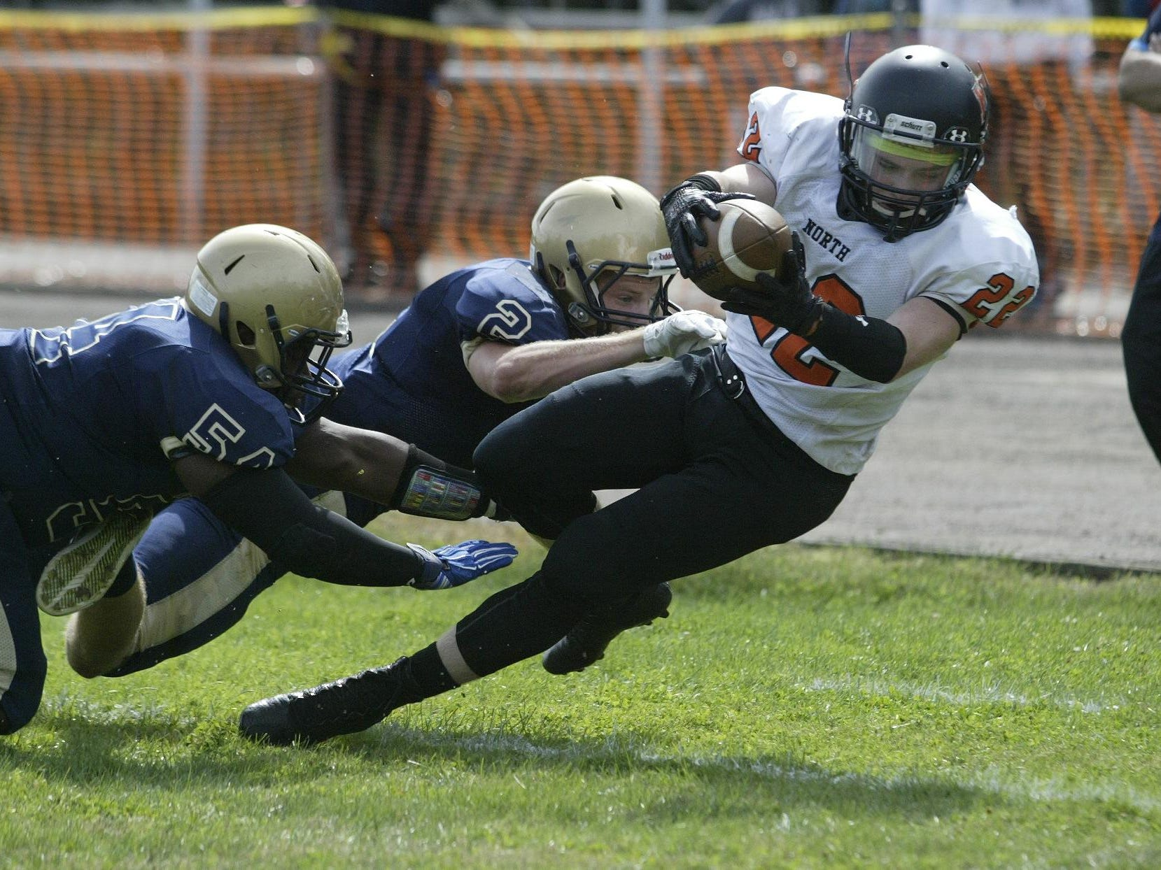 Middletown North High School running back Connor Welsh dives just short of the end zone while being tacked by Freehold's Jake Curry (#2) and Marki Gill #54 (left) during a Shore Conference game, Saturday afternoon, at Freehold.