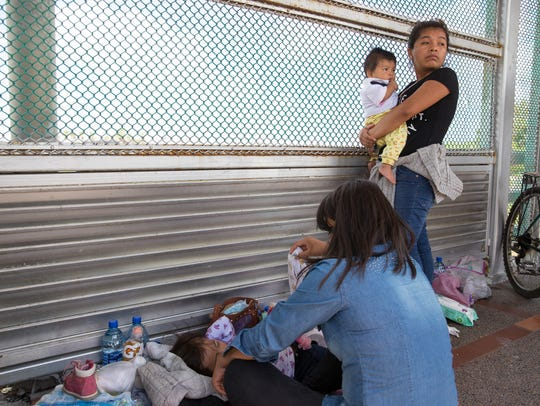 Two Guatemalan women and their children seeking asylum wait on the Mexican side of the international bridge to Brownsville Texas on Wednesday, June 27, 2018.