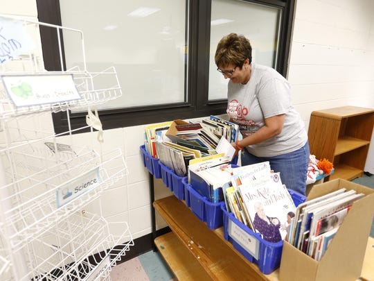 First grade teacher, Cathy Richardson at Truman Elementary School, moves books from her old classroom into a new one.