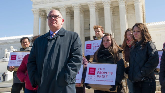 "Jim Obergefell, front, the named plaintiff in the marriage equality case Obergefell v. Hodges, speaks in front of the U.S. Supreme Court on March 6, 2015, as the Human Rights Campaign delivers its historic ""people's brief,"" with 207,551 signatories calling for full nationwide marriage equality."