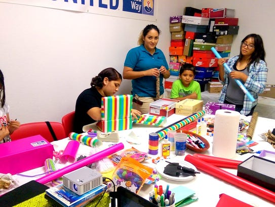 United Way volunteers assemble Shoebox care packages