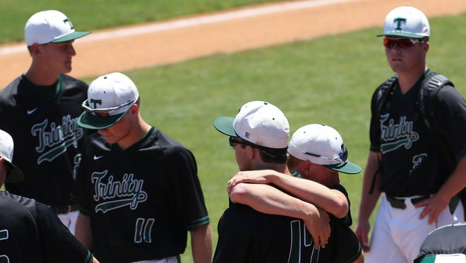 Trinity's Max Medley (14) embraced teammate Mike Blair (17) after they were defeated by McCracken County 1-0 during the KHSAA State Baseball Tournament.  June 9, 2017