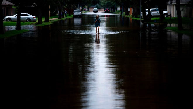 A woman walks down a flooded road during the aftermath of Hurricane Harvey on August 30, 2017 in Houston, Texas.