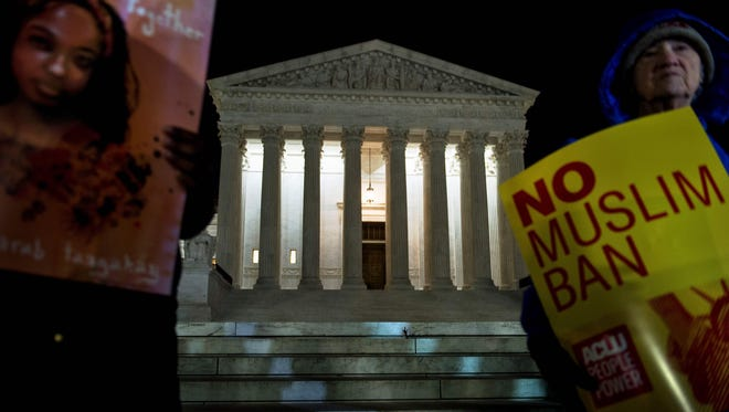 Demonstrators protest against President Trump's travel ban outside the Supreme Court Thursday night. Two federal appeals courts heard oral arguments in the case this week.