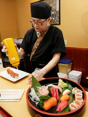 Chef Charlie Hung prepares sushi for his customers