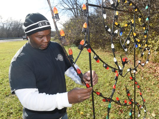 Don Williams of Wayne County Parks checks multi-colored light bulbs. The display will be open throughout the holiday season, except Christmas Day.