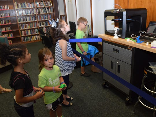 Lenora August (8, left), Cecelia Olagues, 4, Kylie Bush, 9, and Owen Edwards, 8, look at a at 3-D printer at the Rapides Parish Library in downtown Alexandria. All are campers at the T.R.E.E. House Children's Museum's science camp being held this week.
